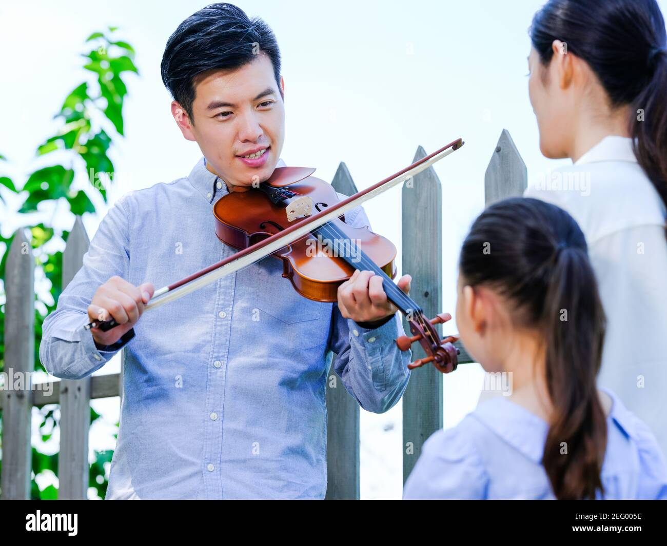 Un homme jouant du violon dans le parc avec sa femme et fille Banque D'Images