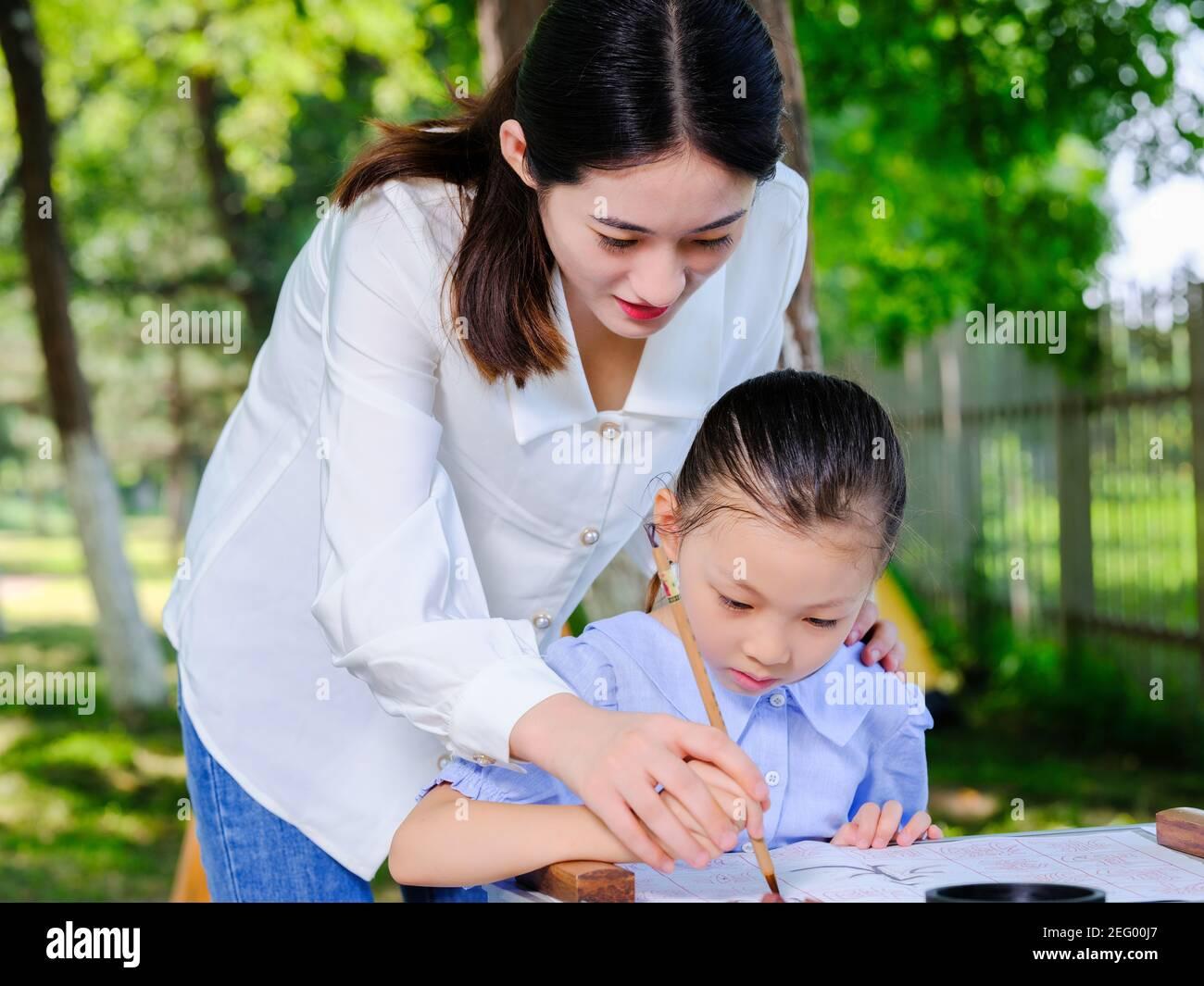 Bonne mère et fille écrire calligraphie à l'extérieur sans regarder le appareil photo Banque D'Images
