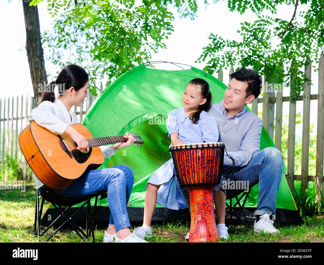 Bonne famille de trois joueurs de guitare dans le parc avec une tente Banque D'Images
