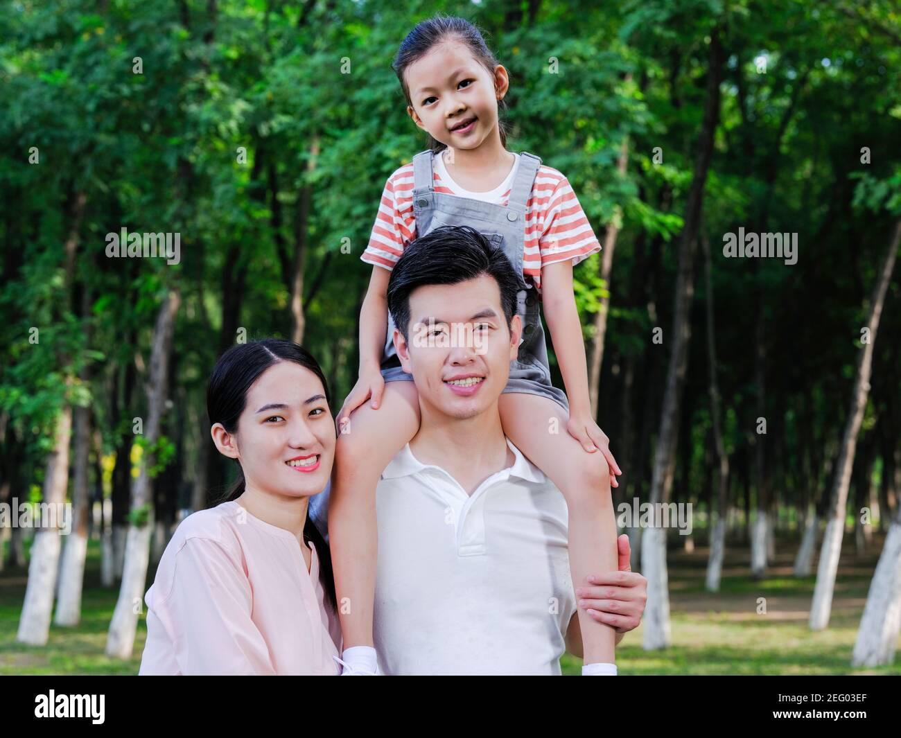 Une famille heureuse de trois personnes jouant dans le parc la caméra Banque D'Images