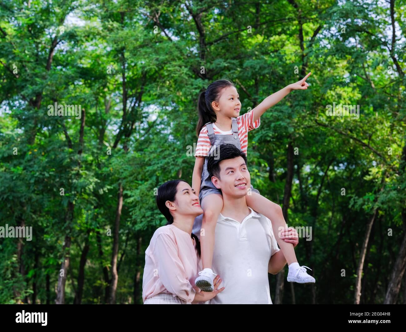 Famille heureuse de trois personnes debout dans le parc pointant Banque D'Images