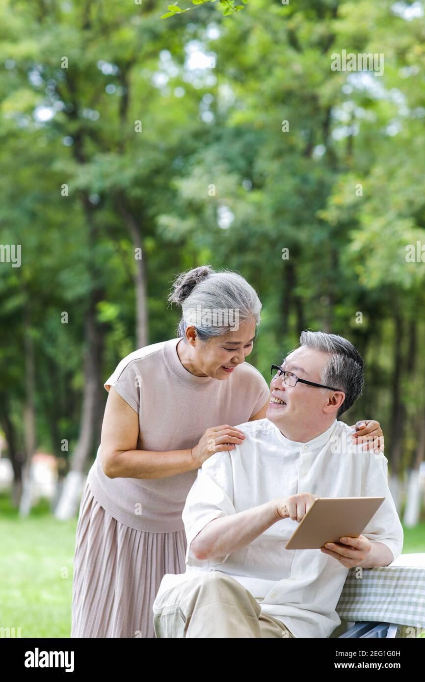 Les couples de personnes âgées heureux utilisent des tablettes électroniques dans le parc Banque D'Images