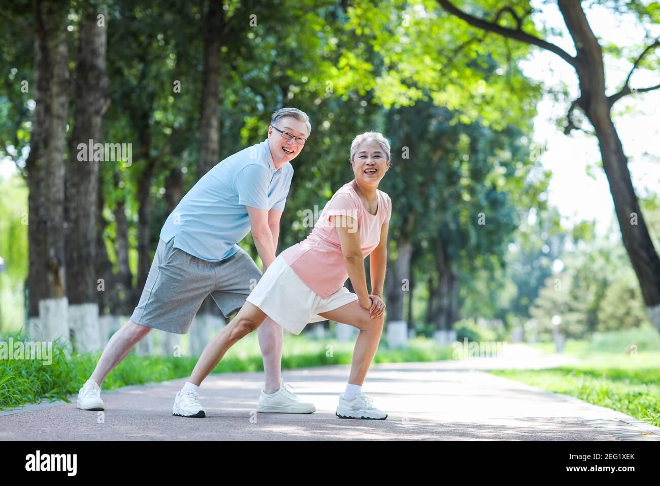 Vieux couple sportif dans le parc souriant Banque D'Images