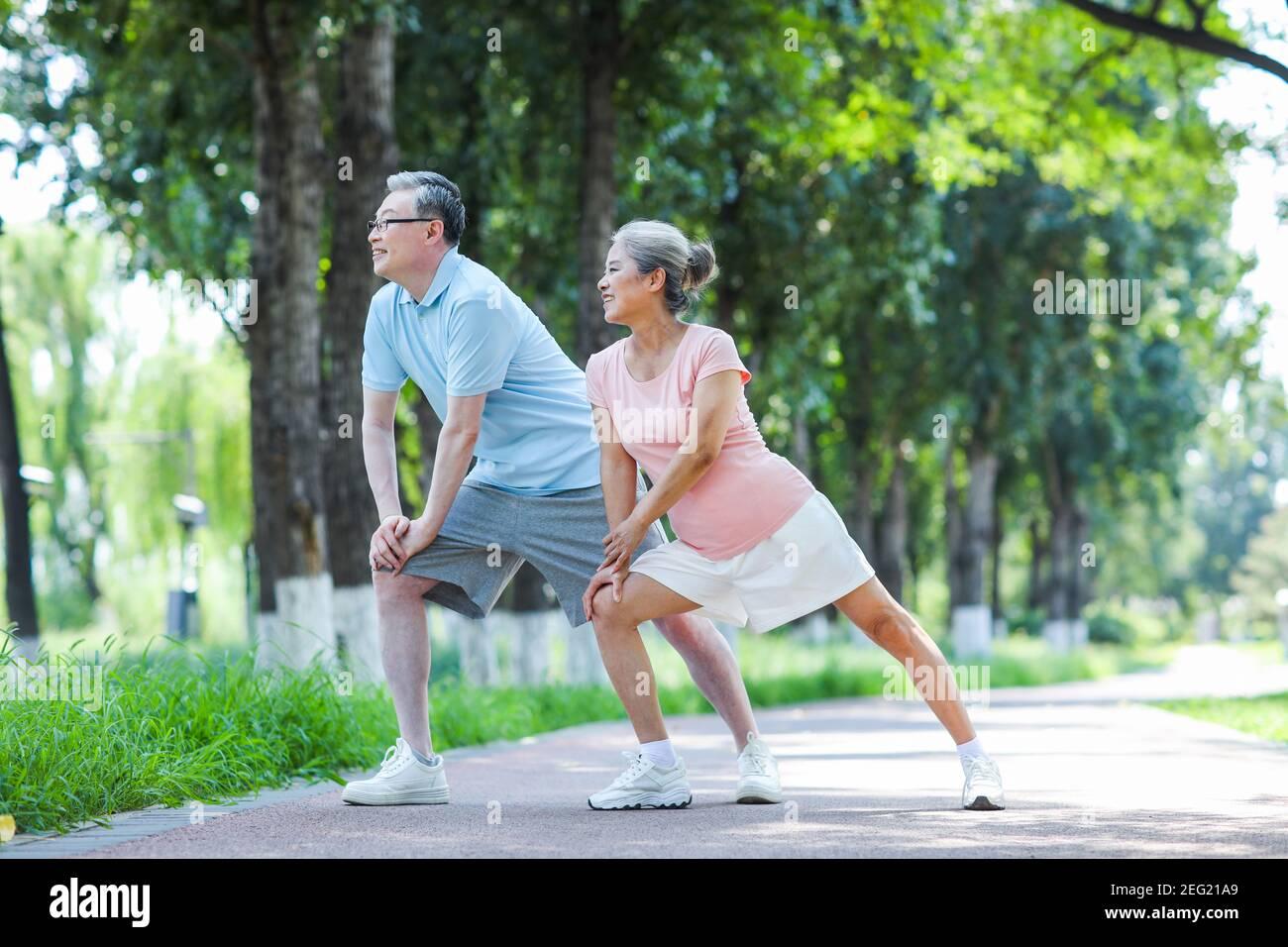 Un vieux couple fait de l'exercice dans le parc Banque D'Images