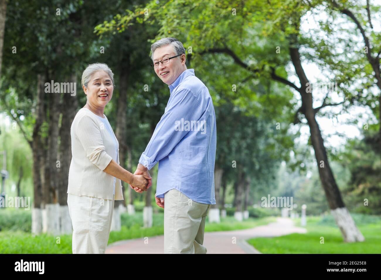Bon vieux couple qui marche dans le parc main dans la main Banque D'Images