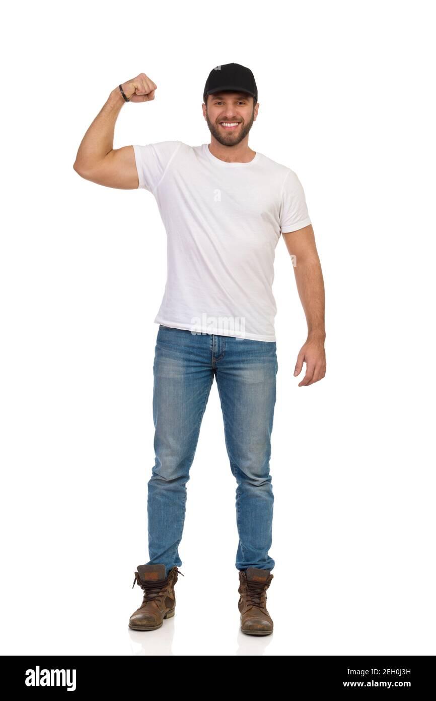 Décontracté jeune homme en casquette noire, chemise blanche, jeans et bottes brunes est debout, flexible biceps, regardant l'appareil photo et sourire. Vue avant. Longueur totale Banque D'Images