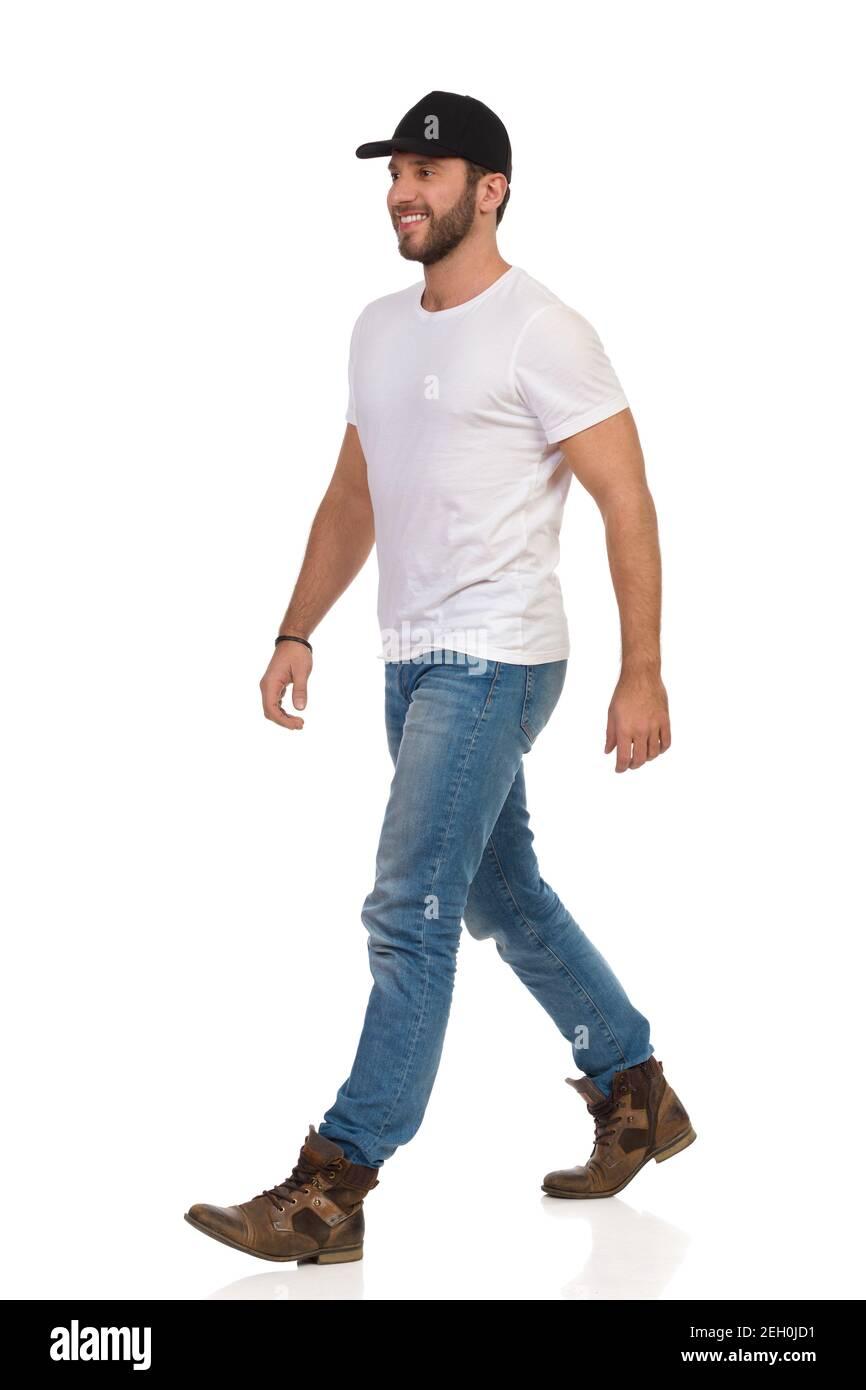 Décontracté jeune homme en casquette noire, chemise blanche, jeans et bottes marche, regarder loin et sourire. Prise de vue en studio sur toute la longueur isolée sur blanc. Banque D'Images
