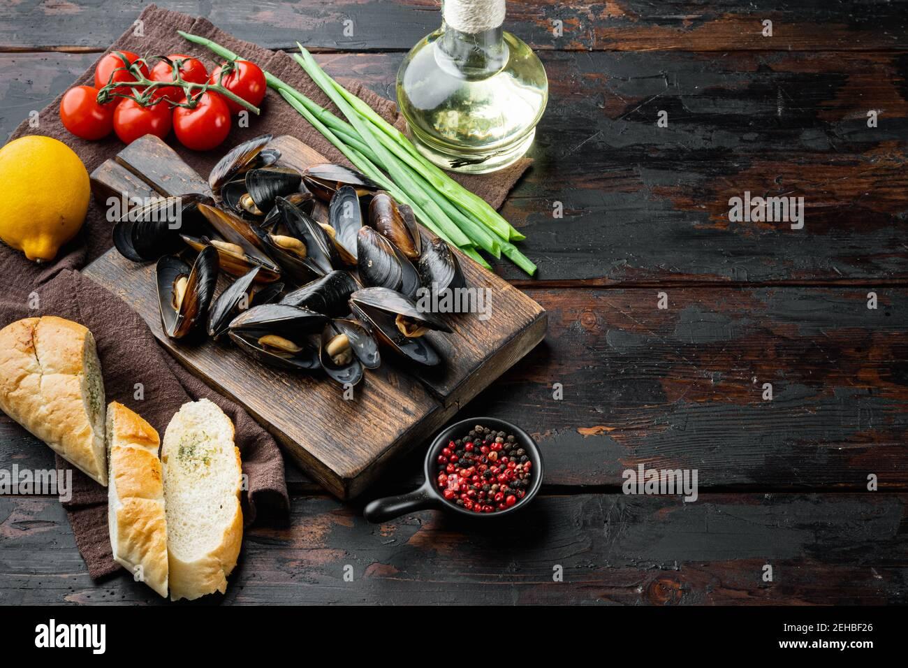 Moules cuites dans la sauce à l'ail avec le persil et l'ingrédient, sur la planche à découper en bois, sur le fond de la table en bois foncé, avec l'espace d'imitation et l'espace FO Banque D'Images
