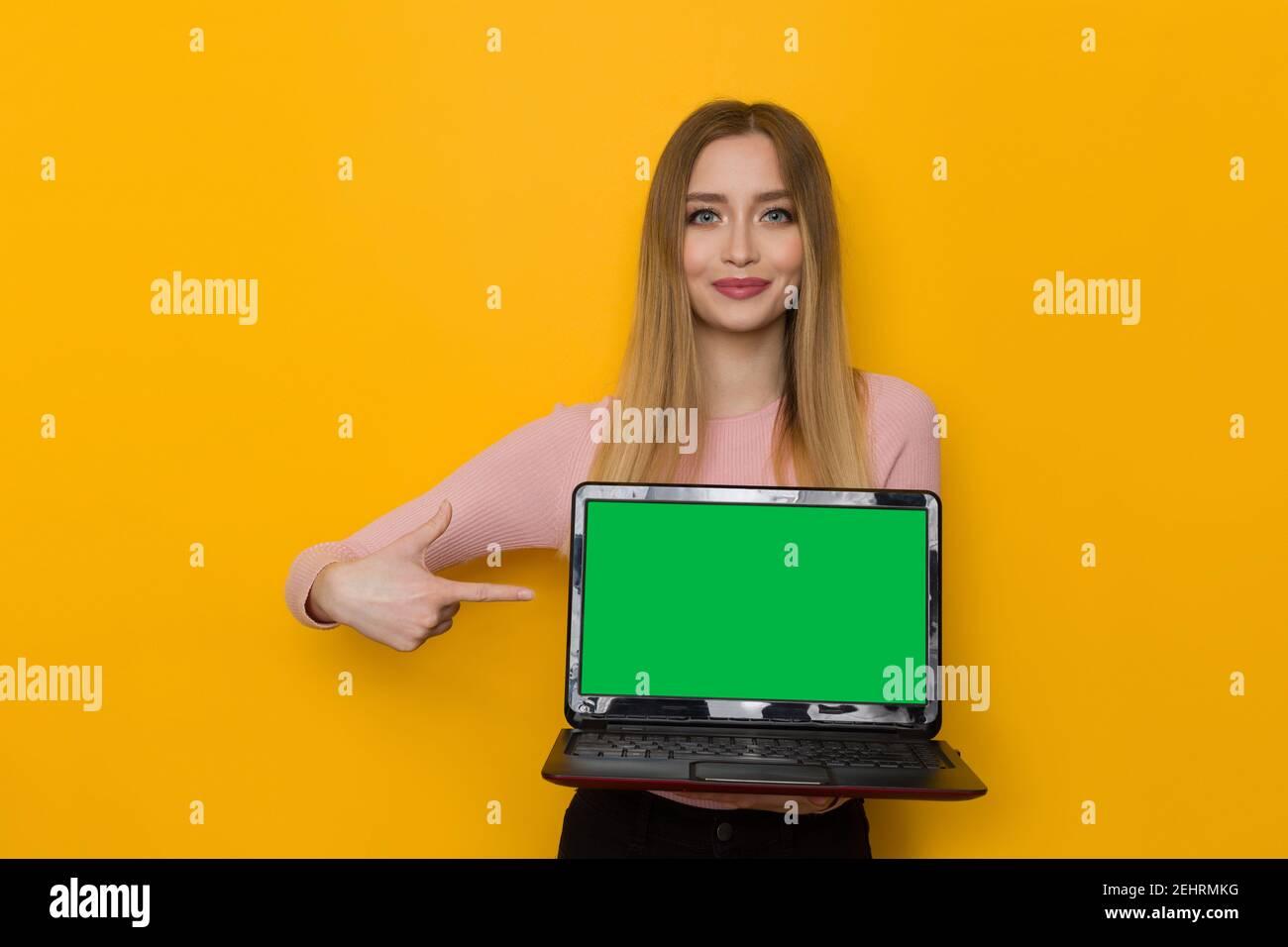 Une jeune femme souriante en chandail rose tient un ordinateur portable avec écran vert et le pointe vers lui. Taille haute studio tourné sur fond jaune. Banque D'Images