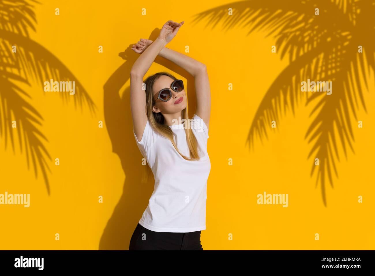 Bonne jeune femme blonde en chemise blanche et lunettes de soleil est debout avec les bras levés contre le mur jaune ensoleillé avec ombre des palmiers. Taille haute. Banque D'Images