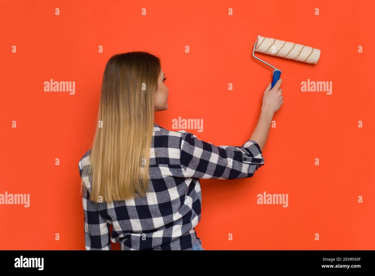 Jeune femme Blonde dans le maillot Lumberjack est peinture mur d'orange avec rouleau de peinture. Vue arrière. Prise de vue à la taille. Banque D'Images