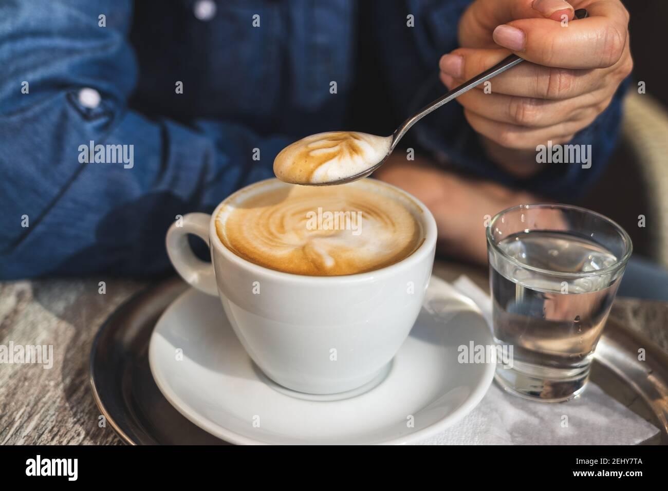 Cappuccino, femme buvant du café au café. Vue rapprochée de la cuillère dans la main féminine et de la tasse de café blanc Banque D'Images