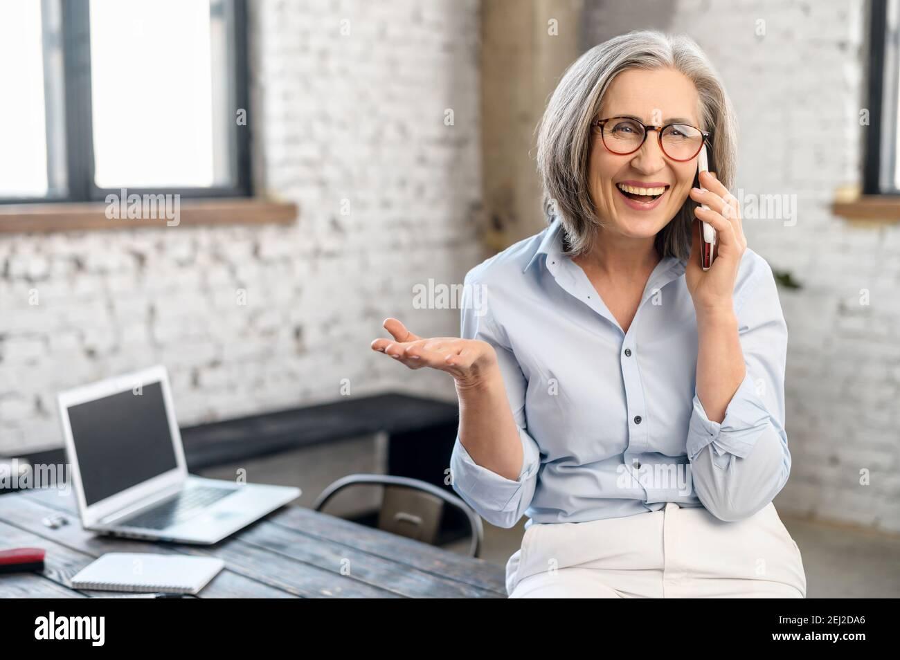 Femme d'affaires moderne et excitée Manager en lunettes et tenue décontractée debout dans le bureau, prendre une pause pour appeler et parler à la famille, tenant Banque D'Images