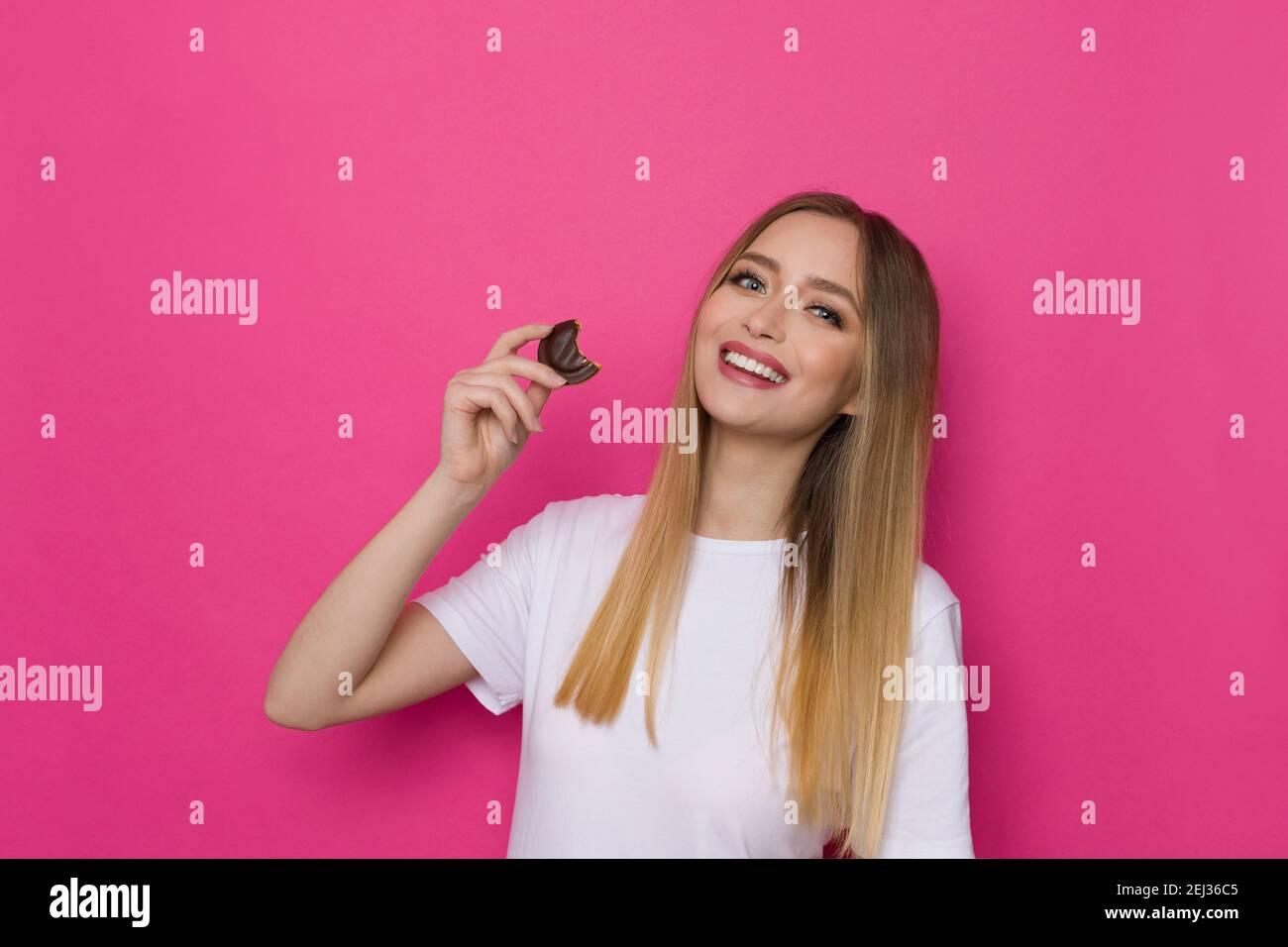 Jolie femme souriante dans un t-shirt qui tient un biscuit au chocolat. Taille haute studio tourné sur fond rose. Banque D'Images
