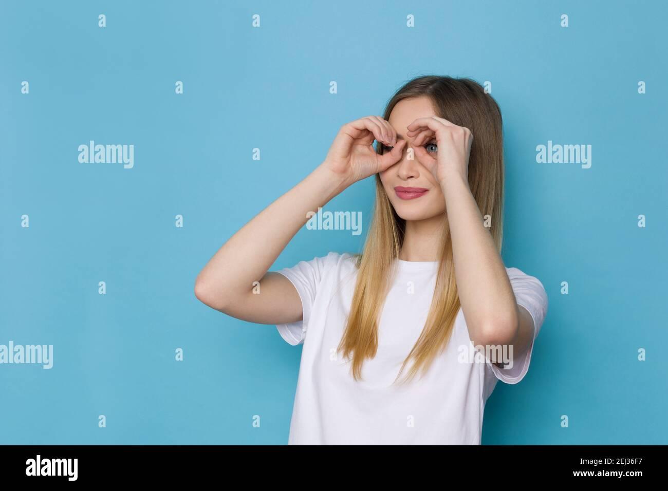 Jeune femme mignonne en chemise blanche fait des jumelles mains et regarde loin. Taille haute studio tourné sur fond bleu. Banque D'Images