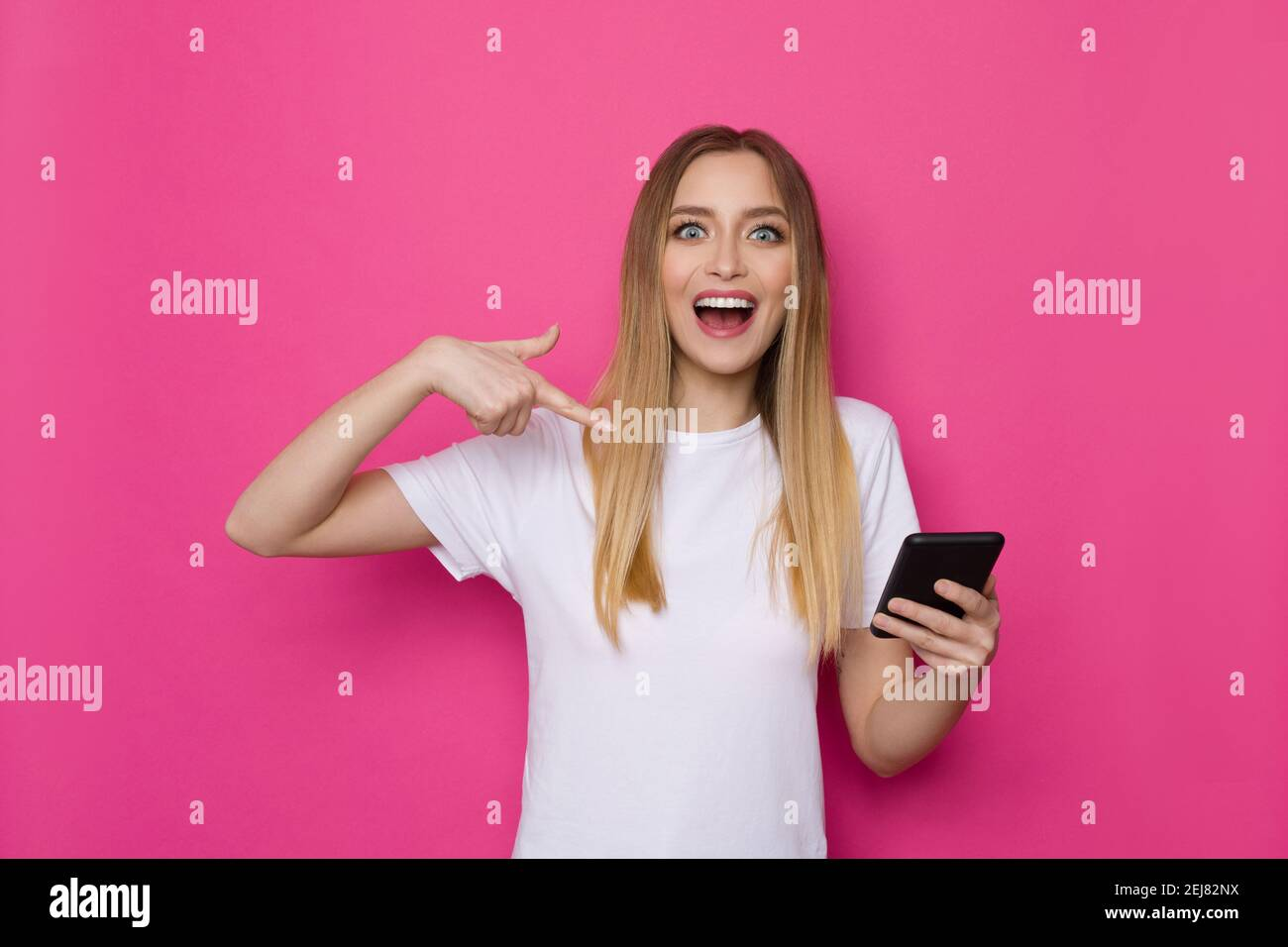 Une jeune femme heureuse en chemise blanche tient le téléphone, le pointe vers lui et crie. Taille haute studio tourné sur fond rose. Banque D'Images