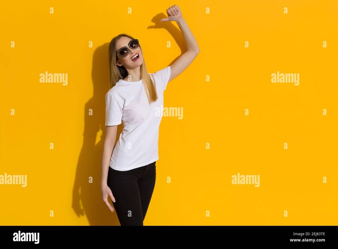 La jeune femme confiante se pointe vers elle avec le pouce et parle. Trois quarts de long studio tourné sur fond jaune. Banque D'Images