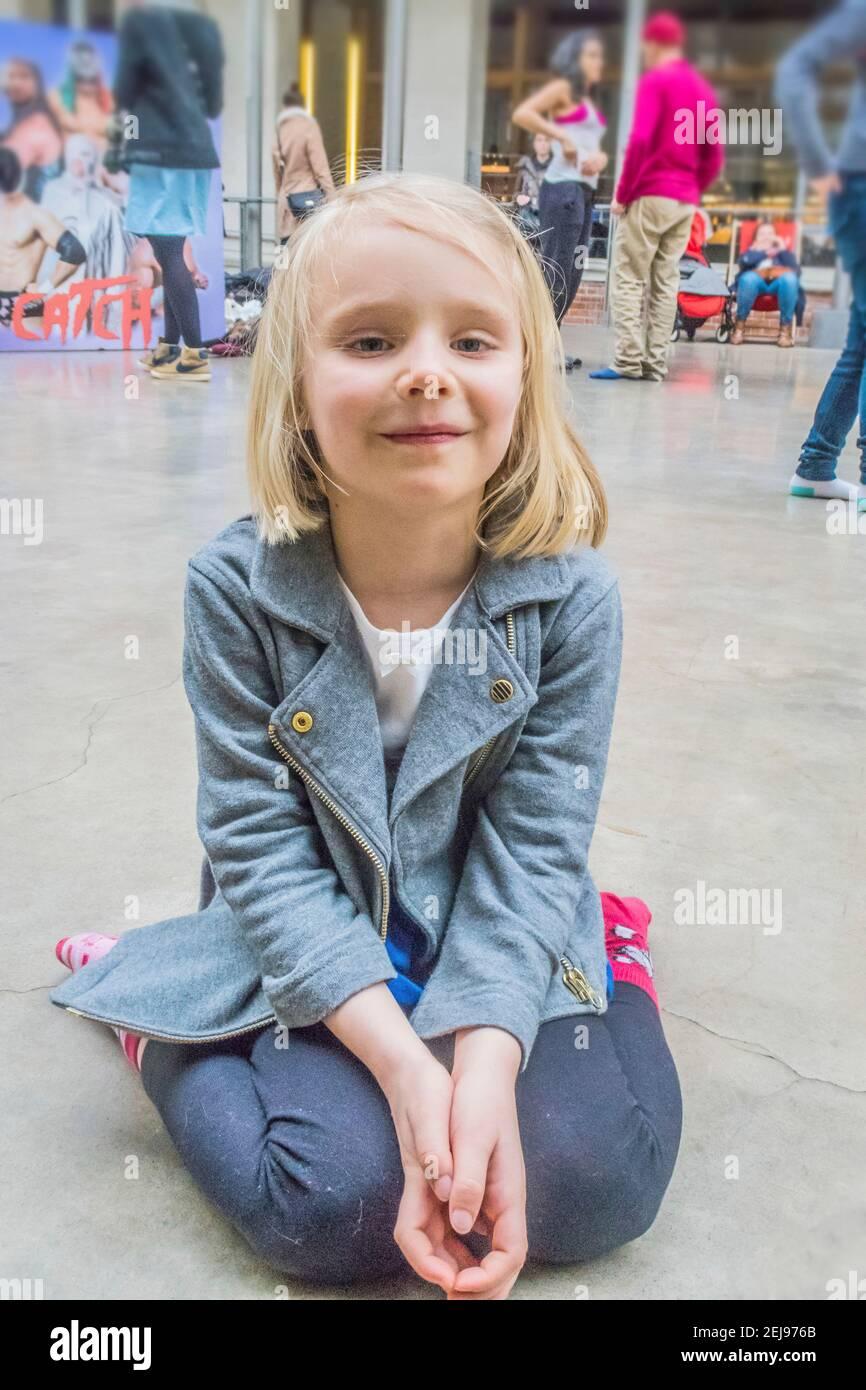 Fille de 5-6 ans sur ses genoux souriant sur un piste de danse Banque D'Images