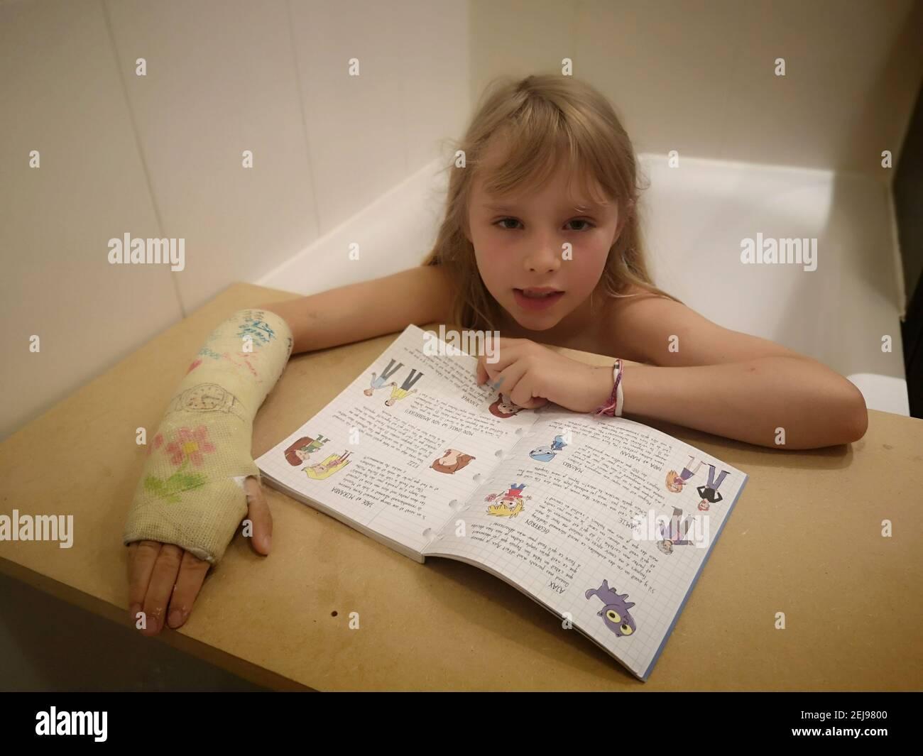 Portrait d'une fillette de 8 ans Européenne au poignet cassé, plateau, lisant sur une nappe en bois un exercice dans son bain , France. Banque D'Images