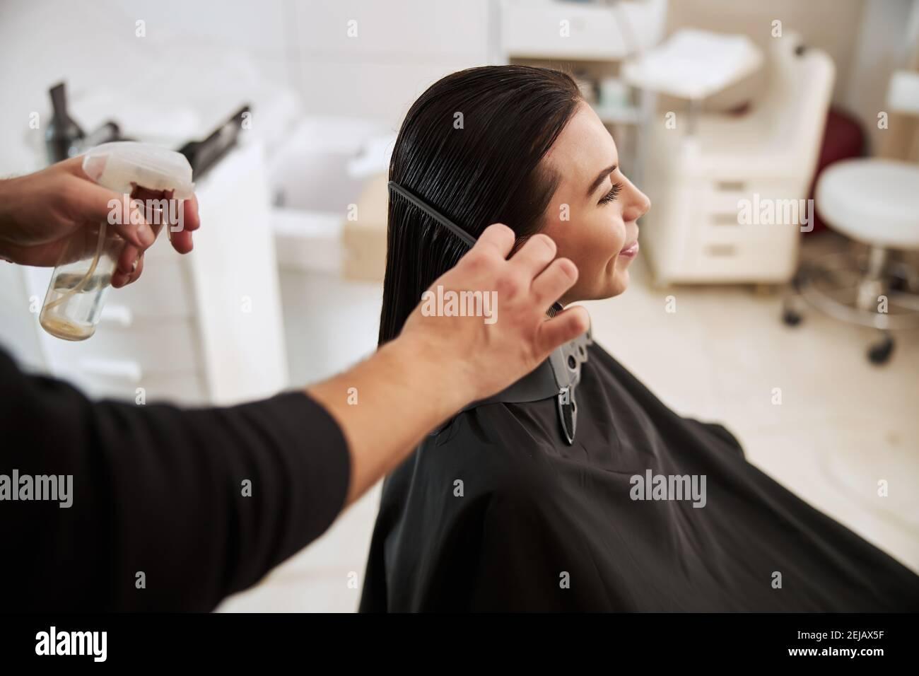 Coiffeur professionnel lissant les cheveux souriants de la femme Banque D'Images