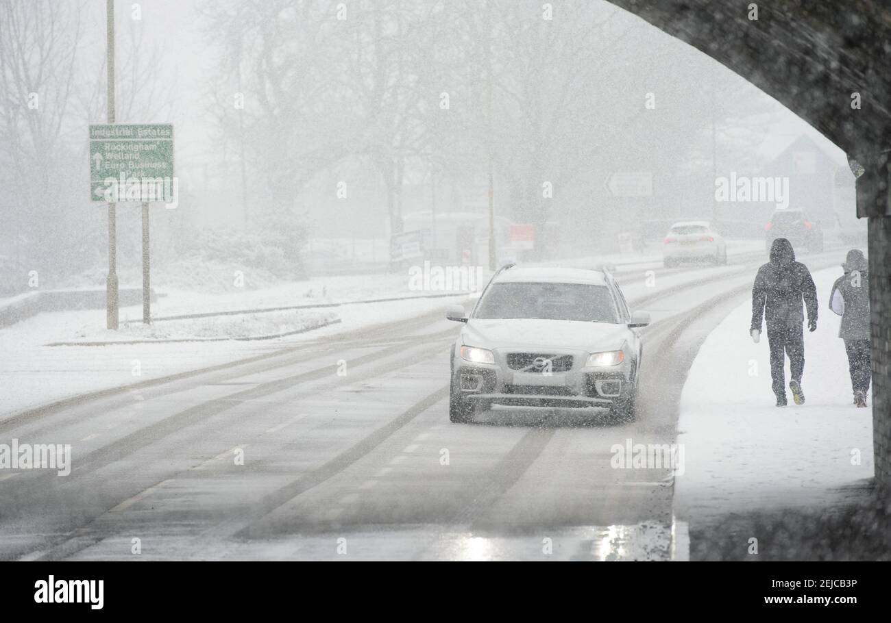 Voitures roulant sur une route enneigée par une journée d'hiver à Market Harborough, Leicestershire, Royaume-Uni. Banque D'Images