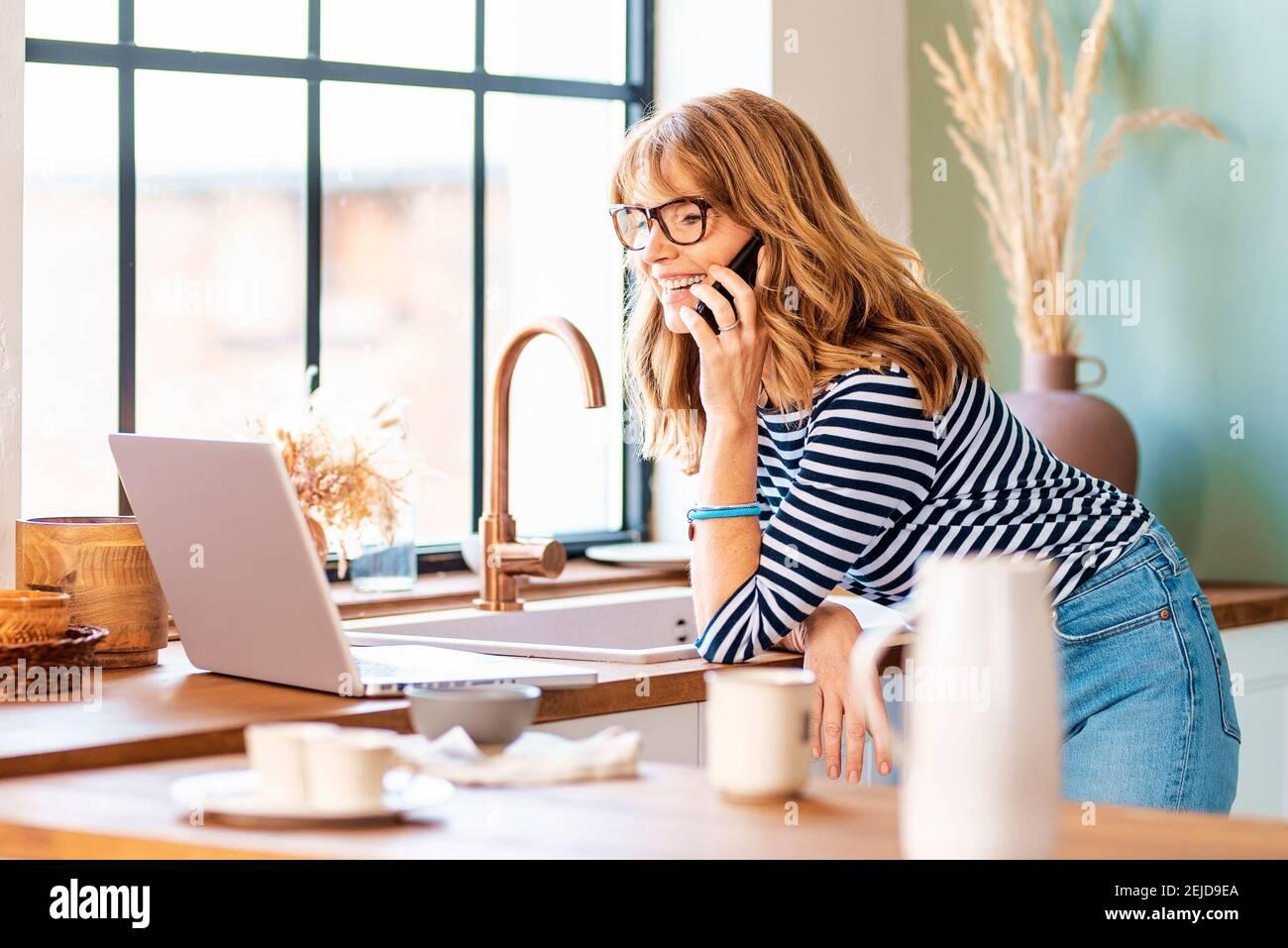 Photo d'une femme d'âge moyen utilisant un ordinateur portable et un téléphone portable dans la cuisine à la maison. Bureau à domicile. Banque D'Images