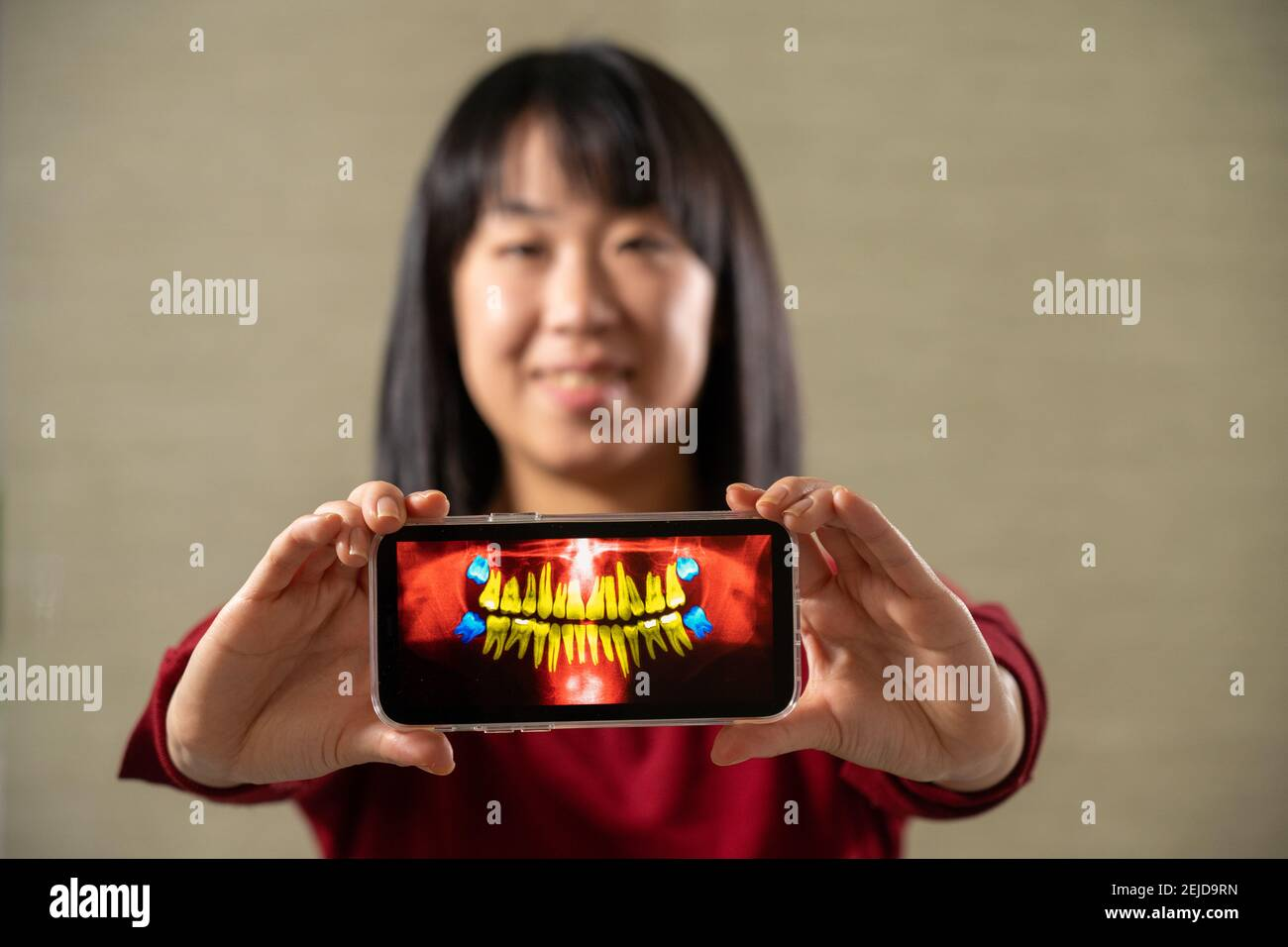 Femme tenant l'écran avec l'image de la dentition adulte Banque D'Images