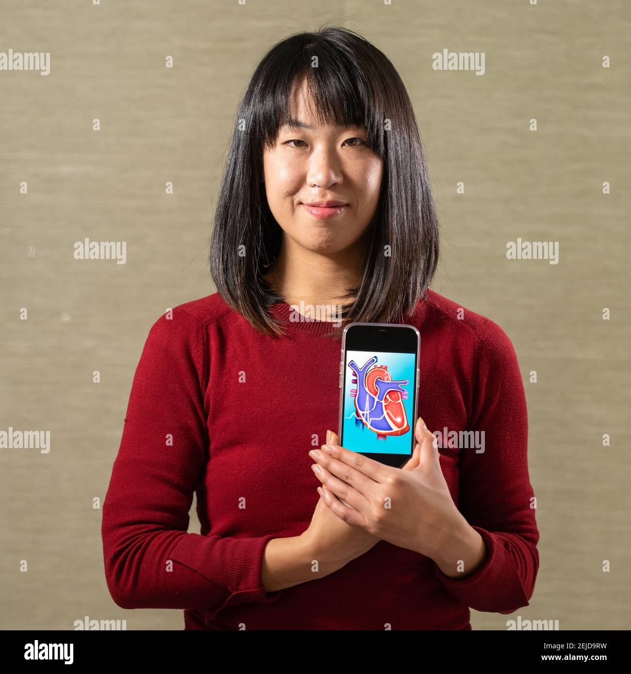 Femme tenant un écran avec un motif coeur découpé Banque D'Images