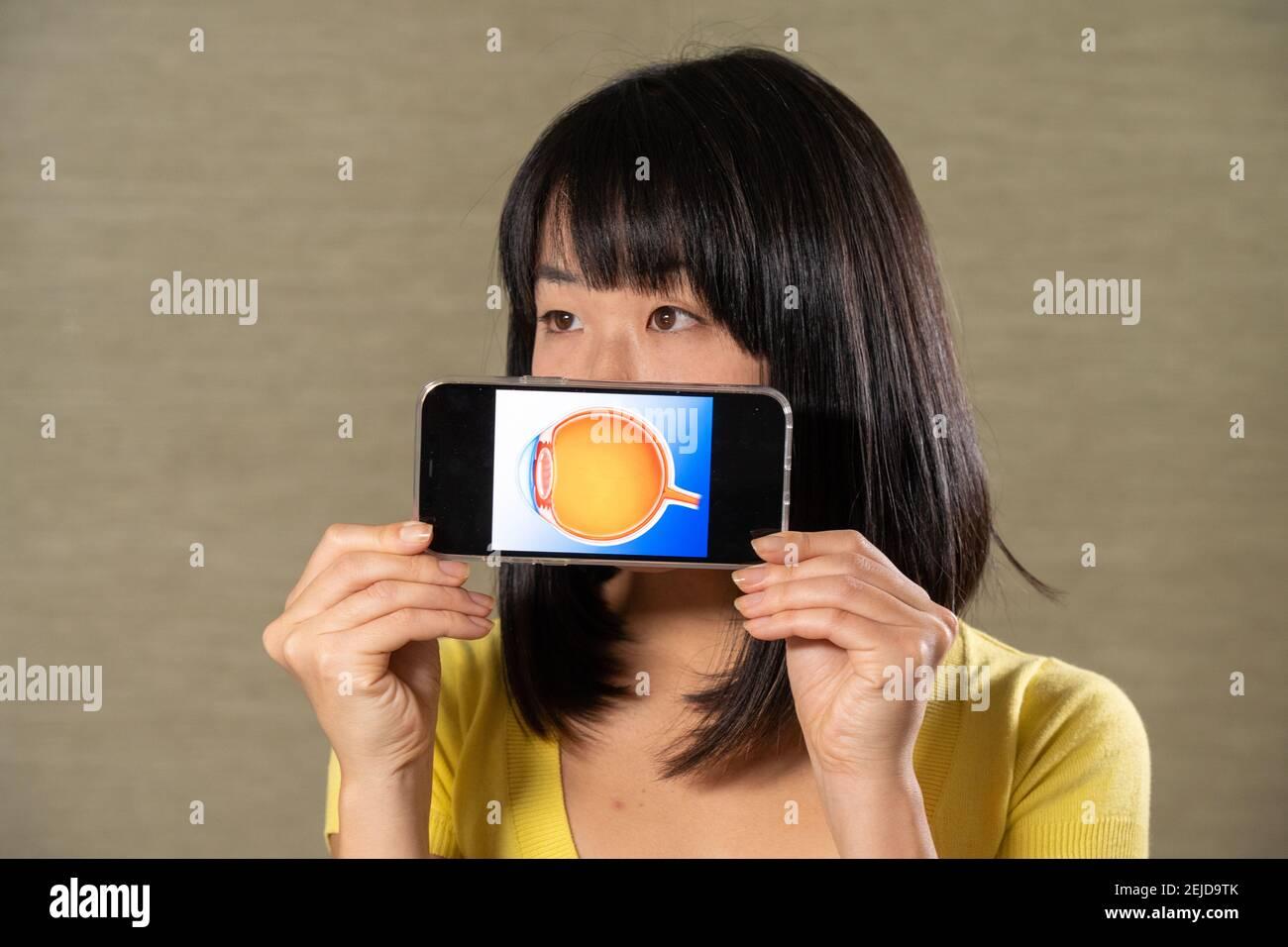 Femme tenant l'écran avec un œil coupé. Banque D'Images