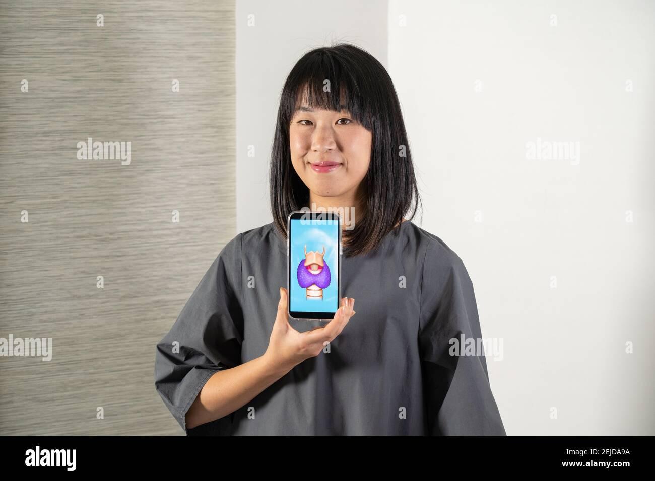Femme tenant l'écran avec dessin de la glande thyroïde et du larynx Banque D'Images
