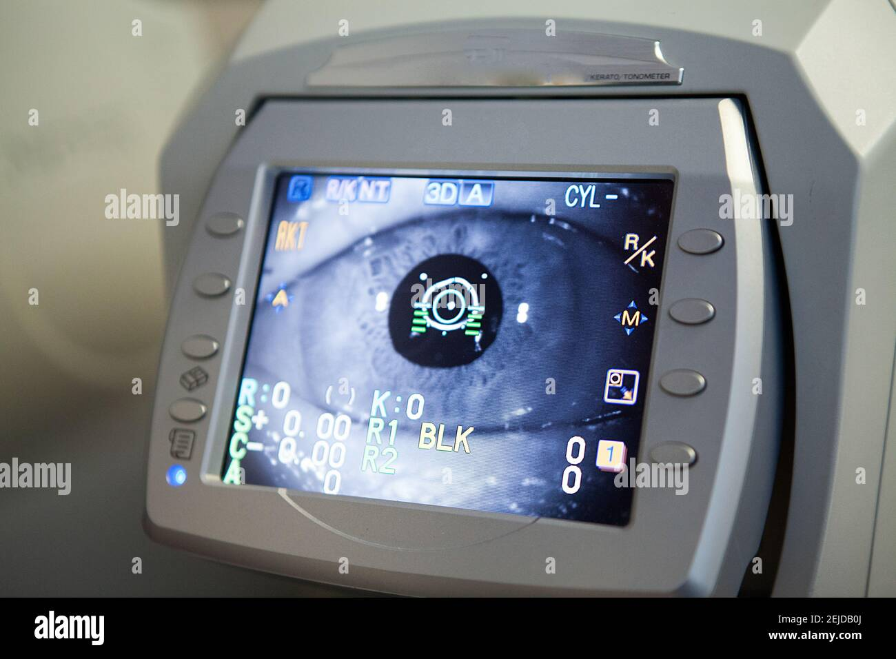 Consultation en ophtalmologie, l'ophtalmologiste effectue une biométrie optique avec un autofracto-kérato-tonometer. Banque D'Images
