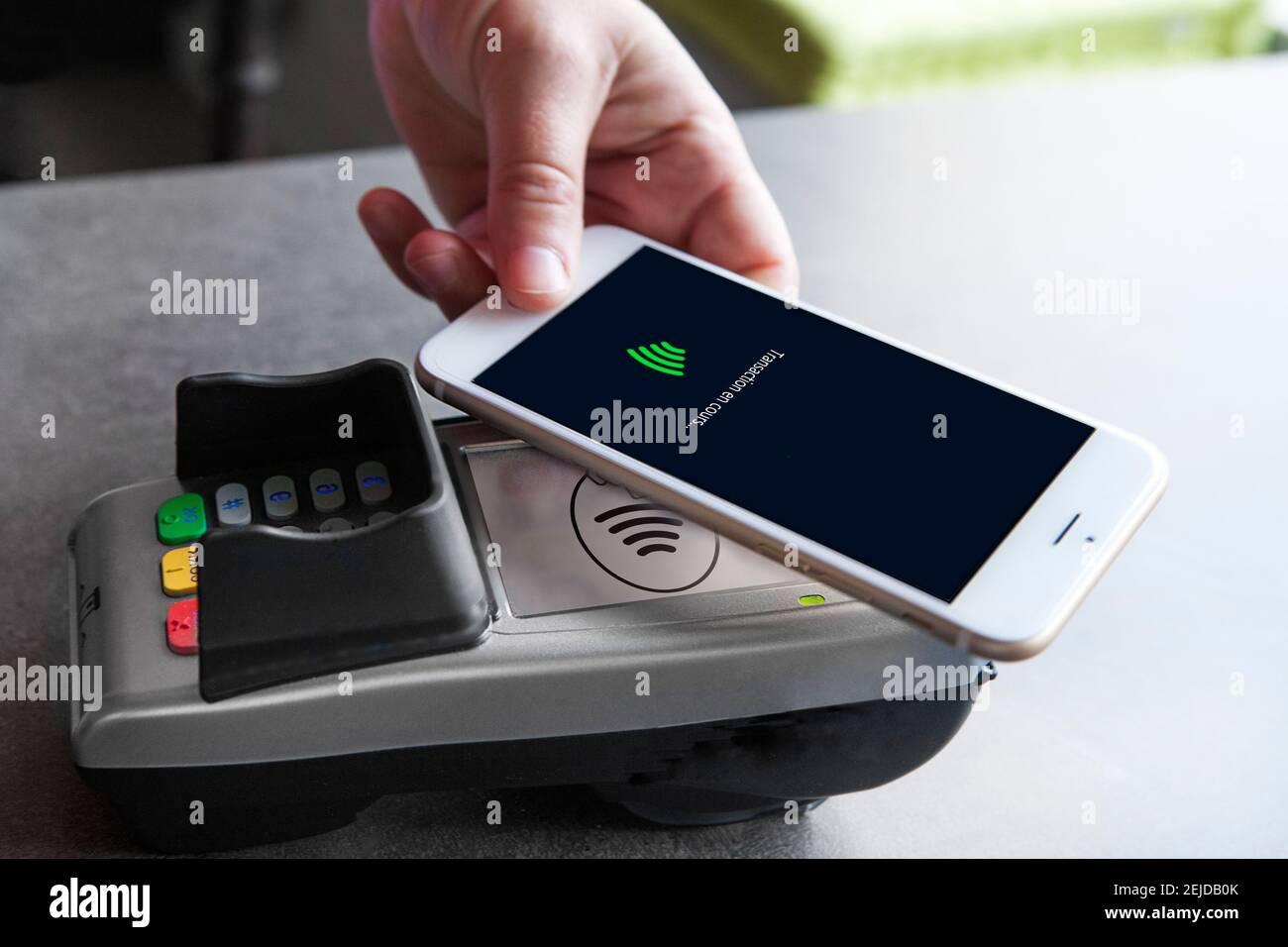 Femme payant avec son smartphone. Banque D'Images