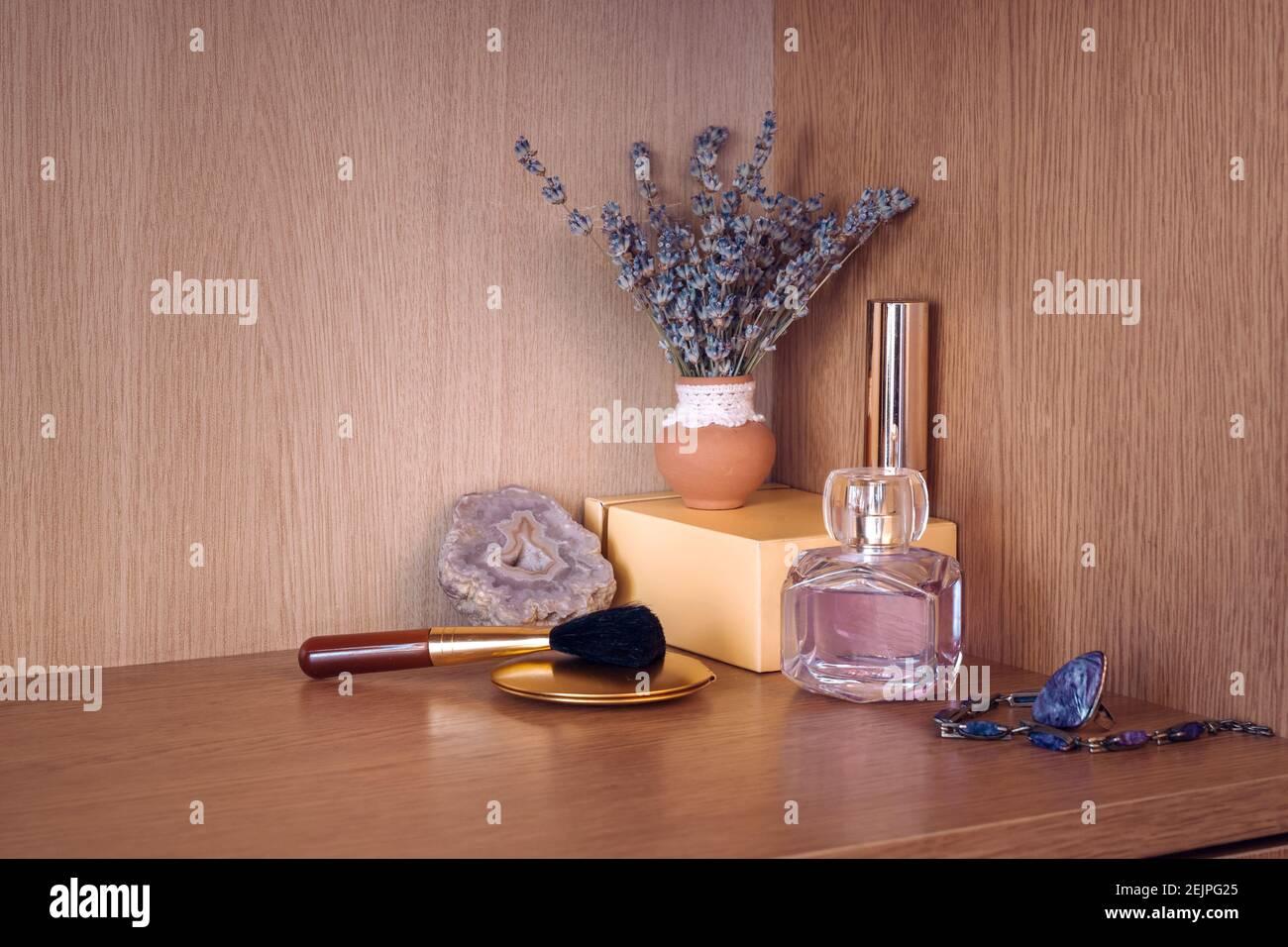 Produits de beauté avec bijoux par vase de fleur de lavanda Banque D'Images