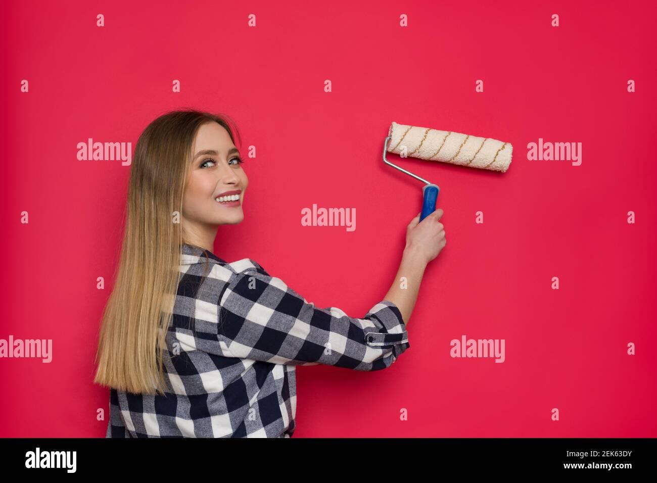 Souriante jeune femme blonde dans la chemise de bûcheron peint le mur rouge avec le rouleau de peinture et regardant la caméra au-dessus de l'épaule. Taille haute. Banque D'Images