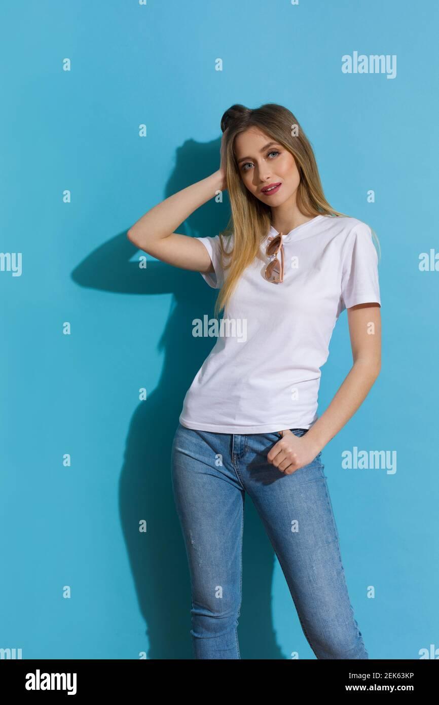 Jeune femme blonde en chemise blanche et jeans est debout dans la lumière du soleil contre le mur bleu. Prise de vue de trois quarts de longueur. Banque D'Images