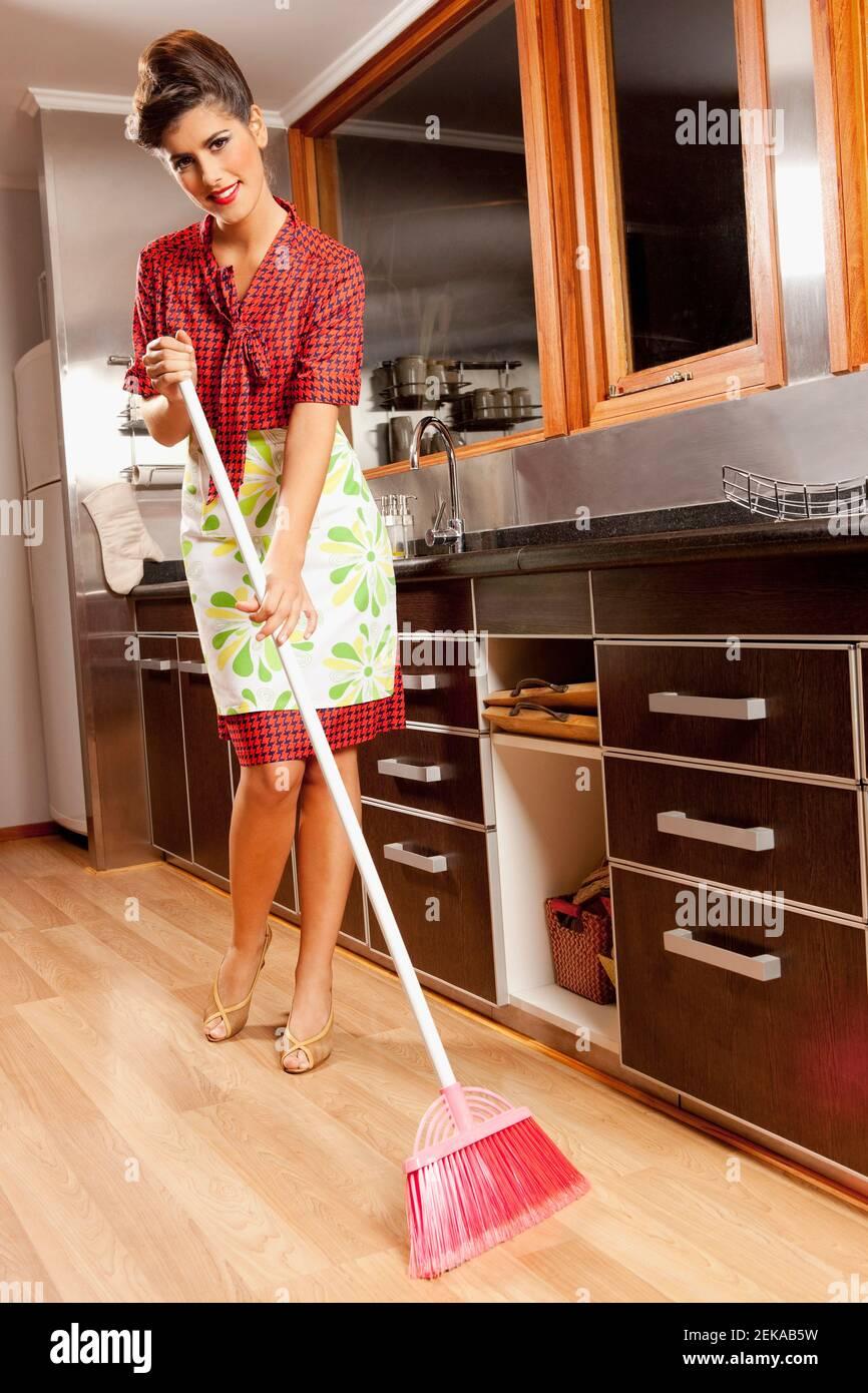 Femme nettoyant le sol d'une cuisine Banque D'Images