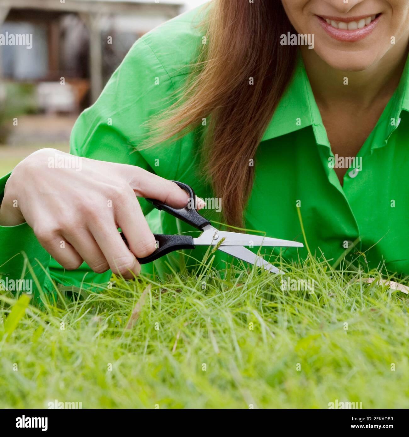 Femme tailler l'herbe avec des ciseaux Banque D'Images