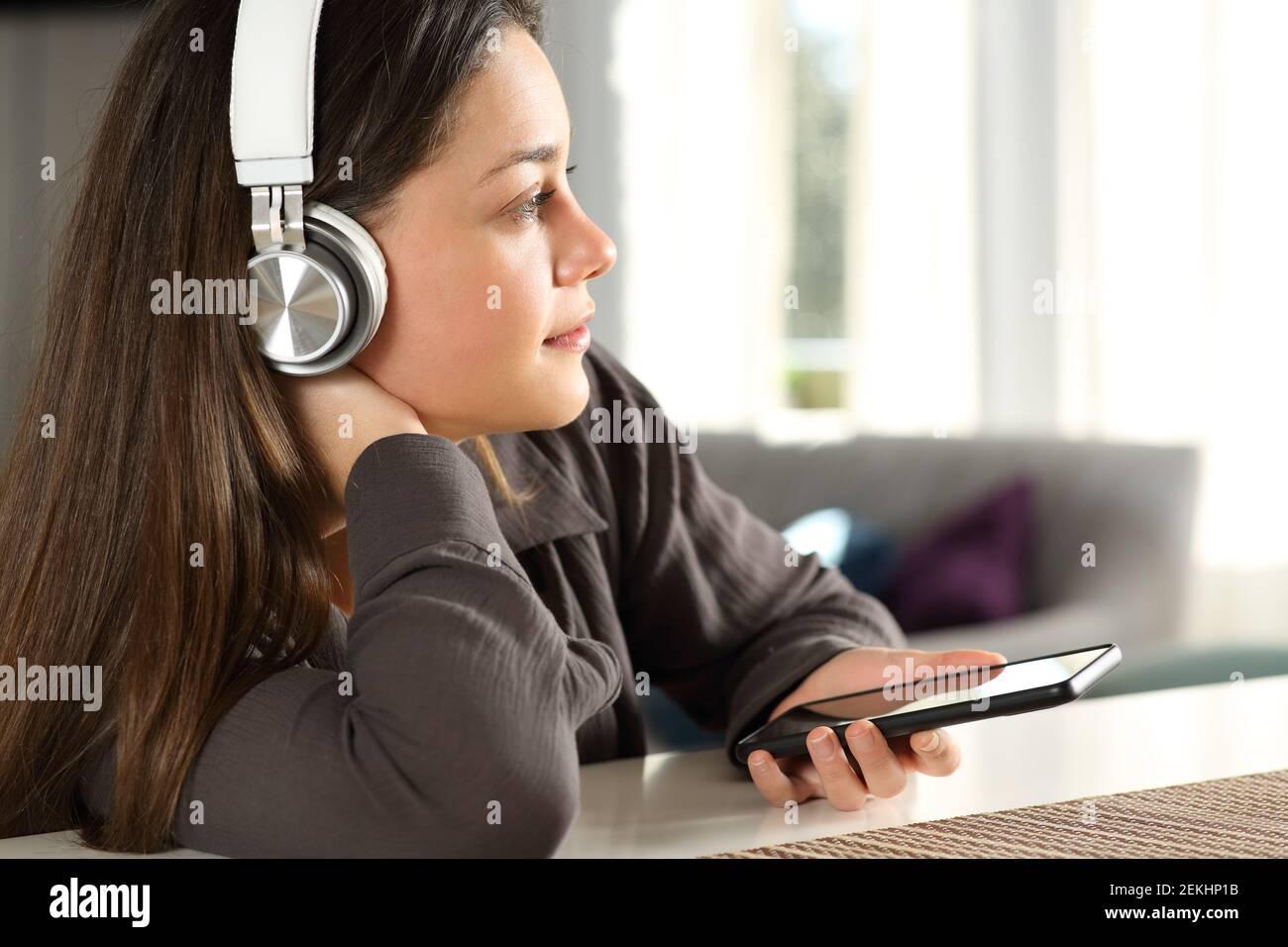 Femme pensive portant un casque sans fil qui envisage d'écouter de la musique à accueil Banque D'Images