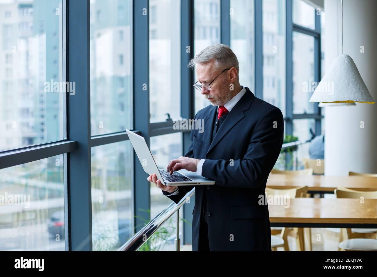 Sourire heureux directeur général pense à son développement de carrière réussi tout en se tenant debout avec un ordinateur portable dans son bureau près de l'arrière-plan d'une victoire Banque D'Images