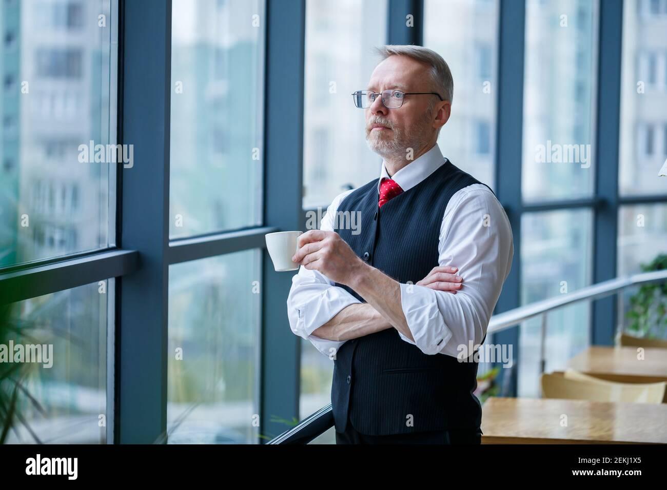 Sourire heureux directeur général pense à son développement de carrière réussi tout en se tenant avec une tasse de café dans sa main dans son bureau près de la Banque D'Images