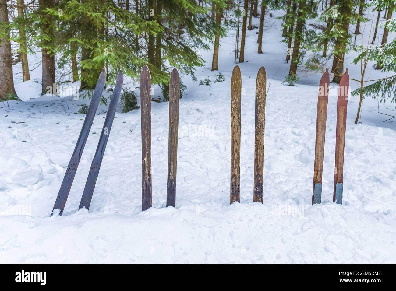 Vieux skis en bois coincés dans la neige dans la partie avant. Arrière-plan des sports d'hiver vintage. Banque D'Images