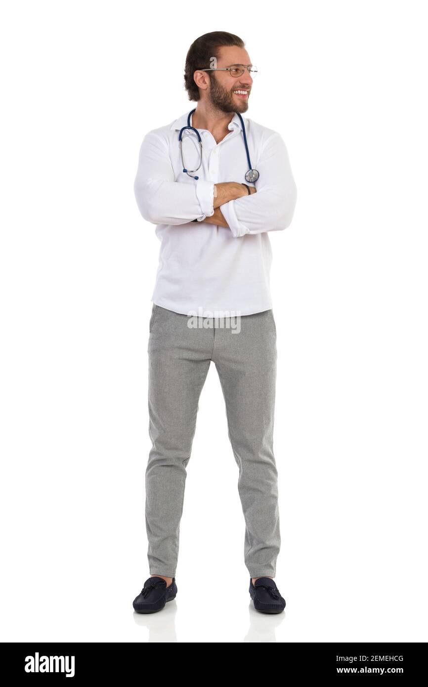 Un jeune médecin souriant est debout avec les bras croisés, regardant sur le côté. Vue avant. Prise de vue en studio sur toute la longueur isolée sur blanc. Banque D'Images