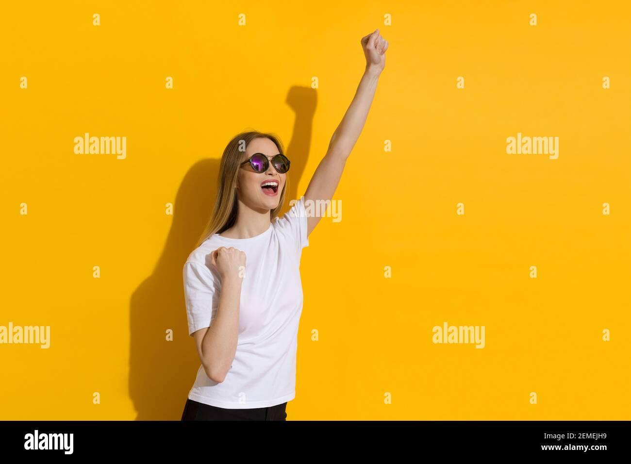 Bonne jeune femme blonde en chemise blanche et lunettes de soleil est debout avec le poing élevé et criant. Taille relevée sur fond jaune. Banque D'Images