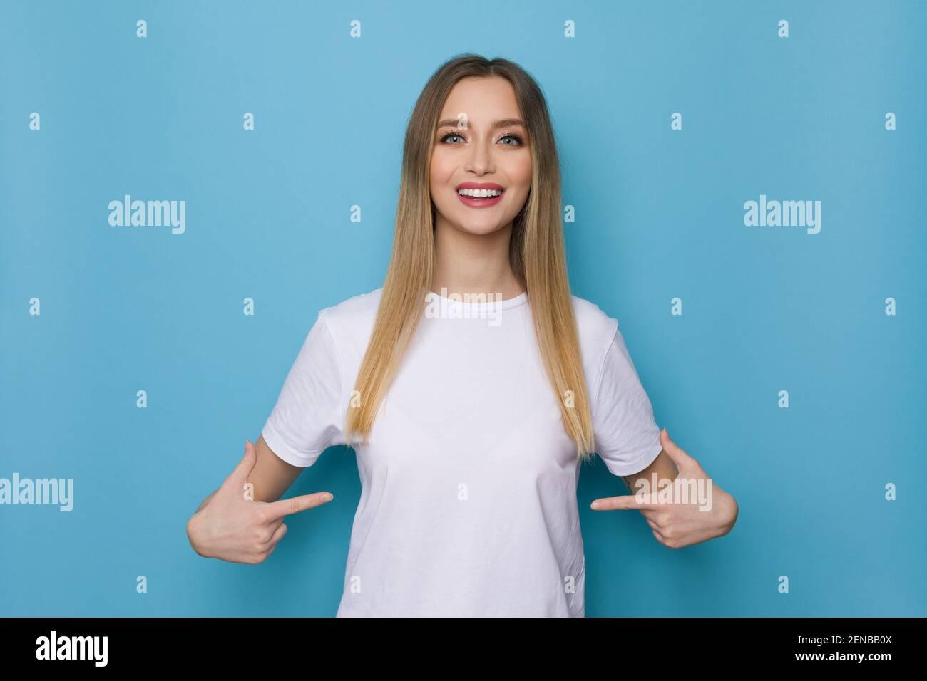 Une fille souriante en chemise blanche se pointe vers elle-même. Taille haute studio tourné sur fond bleu. Banque D'Images