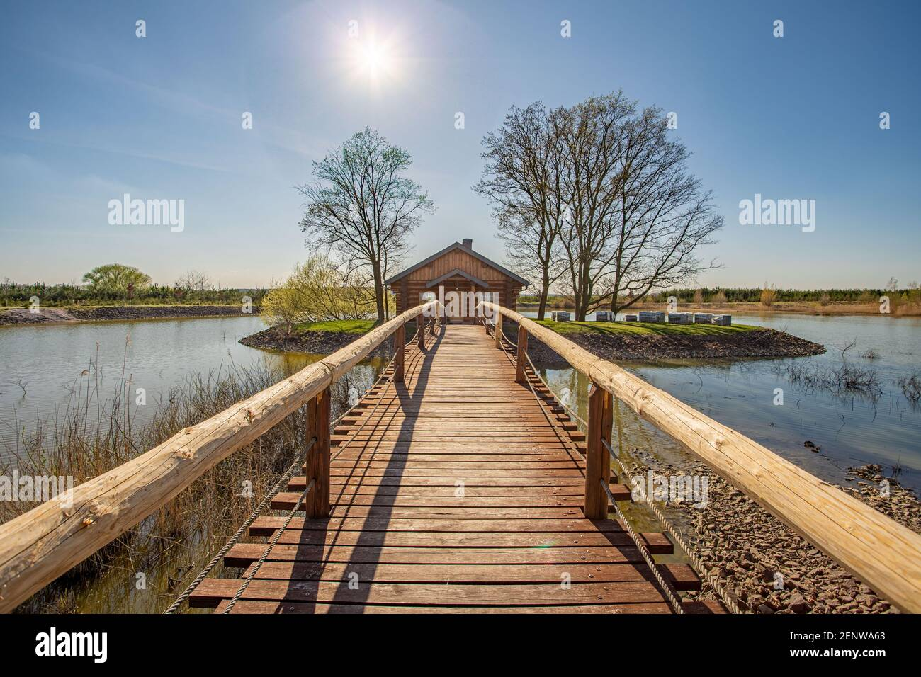 Juin 2020, Kosice, République Tchèque - au milieu du lac il y a une maison dans un petit bosquet, un pont en bois avec des rampes lui mène. L'eau Banque D'Images