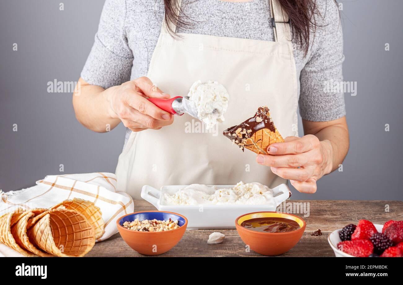 Une femme chef ramasse de glace à la vanille maison sur des cornets de glace à gaufres faits main. Elle a plongé les cônes dans le chocolat fondu et les morceaux de noix f Banque D'Images