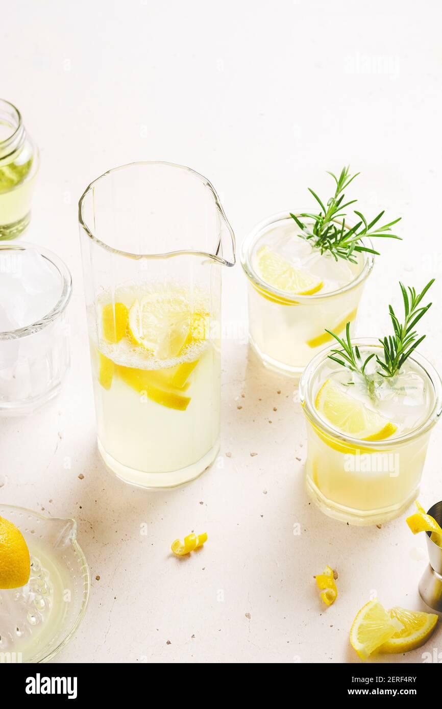 2 verres et une carafe de limonade garnie de zeste de citron et de tranches et de branches de romarin, placés sur un fond blanc avec un espace pour le texte. Banque D'Images