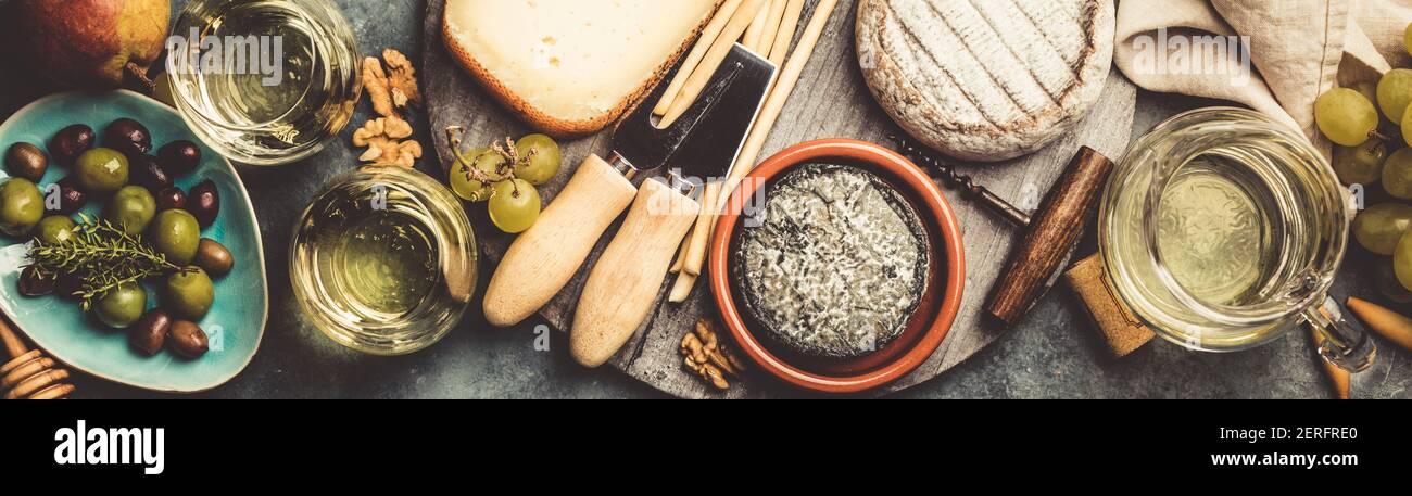 Verres de vin mousseux avec du fromage blanc, les raisins, les noix , les olives et le miel sur fond de béton bleu Banque D'Images