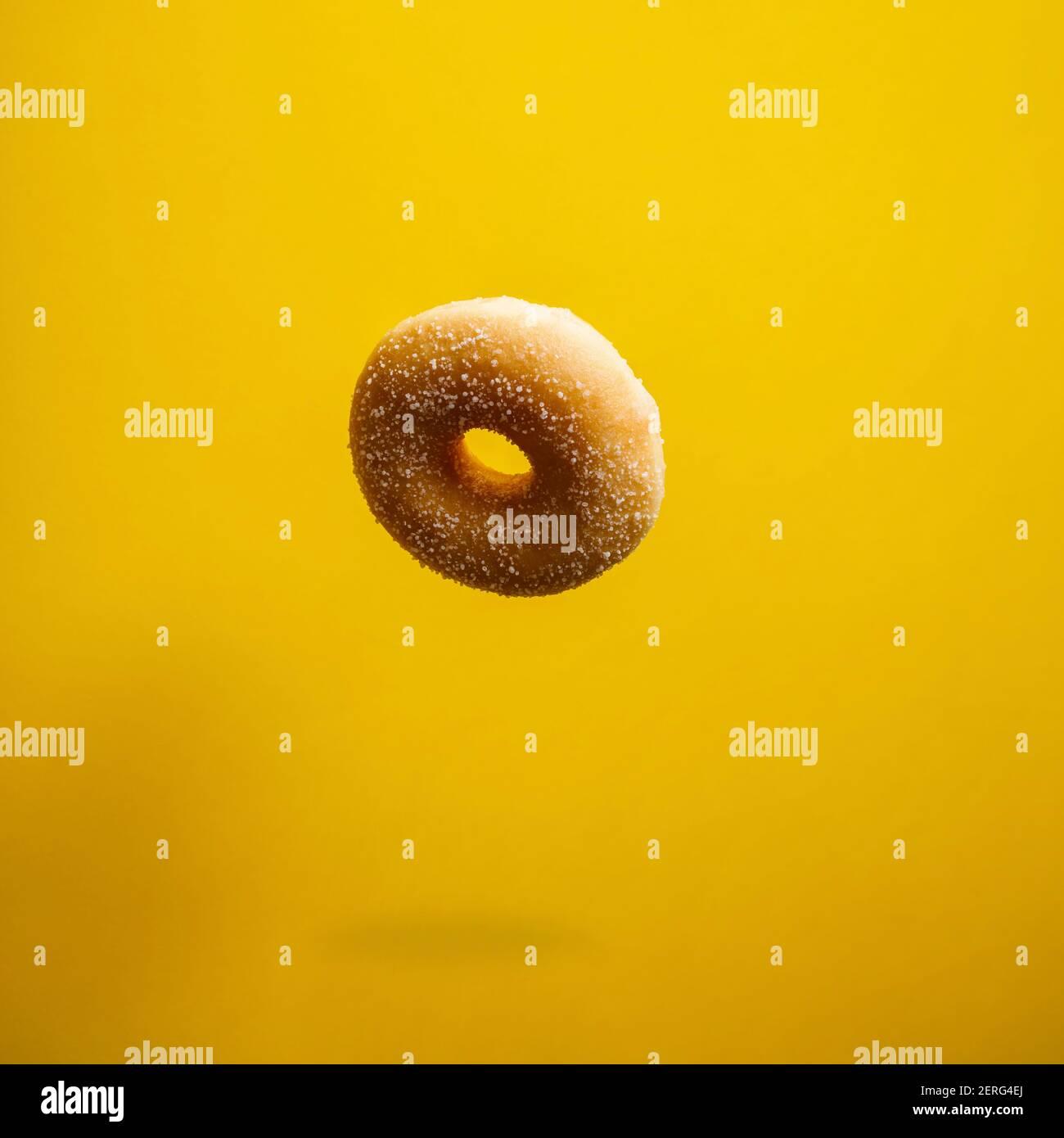 Sugar donut dans motion relevant sur yelloy arrière-plan. Beignets sucrés et colorés en mouvement qui tombent ou qui volent. Banque D'Images