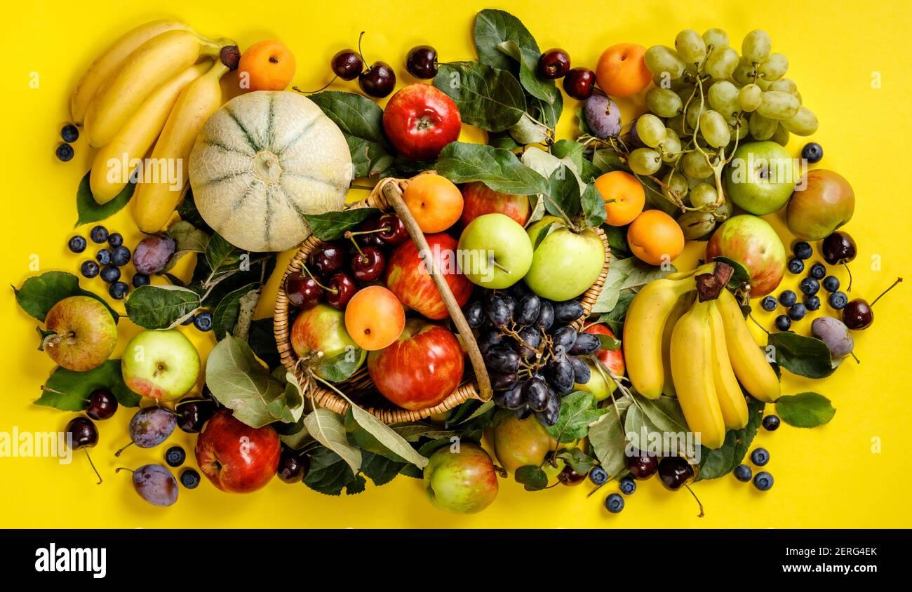 Pondre à plat de fruits frais et de baies sur fond jaune. Vue de dessus. Végétarien, nourriture propre, concept de nourriture crue Banque D'Images